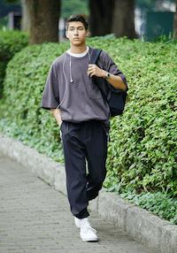 seorang pria mengenakan pakaian oversize dengan gaya memasukan baju ke dalam celana